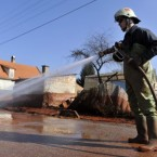 A Hungarian firefighter cleans a street covered by toxic red sludge in Devecser.