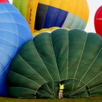 A hot air balloon pilot prepares his balloon for take off near Canterbury, Kent, during a world record-breaking attempt for the largest number of hot air balloons to cross the English Channel.