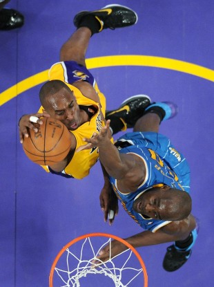 LA Lakers' Kobe Bryant dunks on New Orleans Hornets centre Emeka Okafor last night.