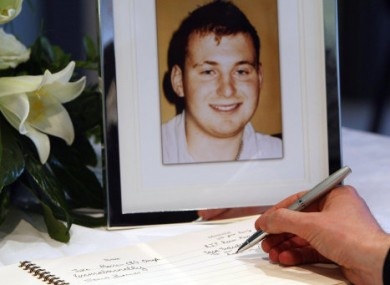 A man signs a book of condolences for Ronan Kerr, pictured.