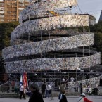 People walk past a tower made of some 30,000 books in different languages, named 