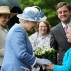The queen receives flowers from 8-year-old Emma Osbourne, watched by the CEO of the National Stud John Osbourne (right) and Chair of the Board of the National Stud Chryss O'Reilly. (Pic:Maxwells/PA Wire/Press Association Images)