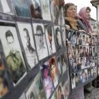 Bosnian Muslim women, survivors of the Srebrenica massacre, hold posters with photos of the missing in June 2006.