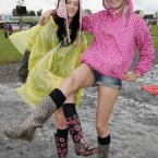 Lorna Hutchman, right, and Orlagh Dooley from Derry enjoying themselves despite mucky conditions at Oxegen today. (Mark Stedman/Photocall Ireland)