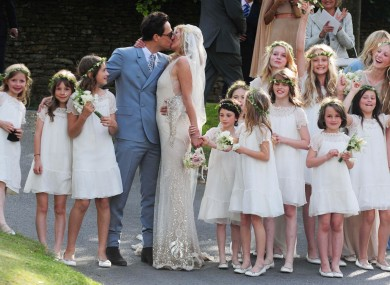 Kate Moss kisses her new husband Jamie Hince (left) after their wedding at St Peter's Church in Southrop.