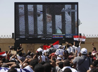 Egypt's ousted President Hosni Mubarak is seen on TV screen as he enters the courtroom on a hospital bed, outside the Police Military Academy complex in Cairo.