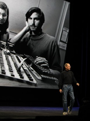 Steve Jobs makes a presentation last year in front of a photograph of himself as a younger man, at the startup of Apple.