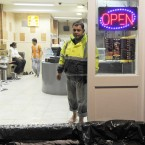 24/10/2011. Flooding. Shoeless staff in a kebab shop in Rathmines try to protect themselves from flooding due to heavy rain. Photo: Laura Hutton/Photocall Ireland