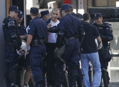 Serbian police officers detain a man, center, as a precautionary measure in downtown Belgrade today