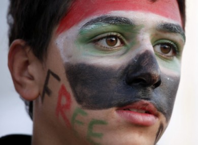 A Syrian teenager wears colors of the national flag at a protest in front of the Syrian embassy in Amman, Jordan
