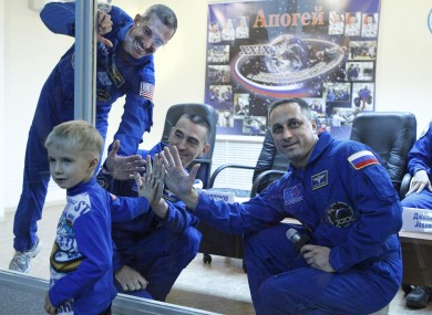 US astronaut Dan Burbank, left, Russian cosmonauts Anton Shkaplerov, right, and Anatoly Ivanishin, centre, hold their hands against safety glass with Maksim, winner of a space poster competition, at the Baikonur cosmodrome prior to the launch.