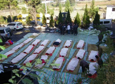 Families grieve over the bodies of 20 of the dead miners recovered from the mine in Yunnan.