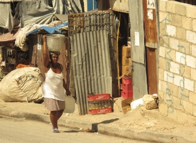 A woman carries a large pot in Baillergeau temporary camp in Haiti