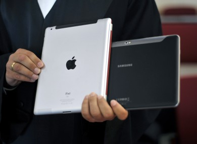 A file photo of a lawyer holding an Apple iPad and a Samsung Tablet-PC at a court in Dusseldorf, Germany.