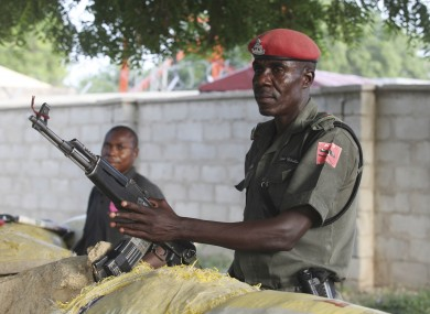 police officers armed with AK-47 rifles stand guard at sandbagged bunkers along a major road in Maiduguri, Nigeria