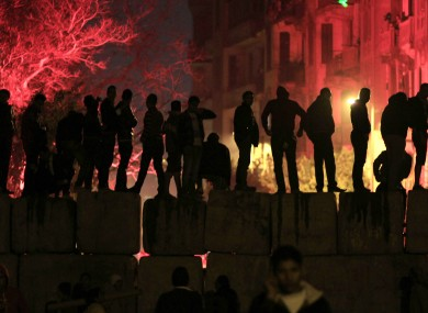 Egyptian protesters stand on a cement block barrier separating the interior ministry from Tahrir Square, Cairo last night.