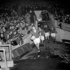 Manchester United captain Bill Foulkes leads the makeshift United team out for their first match since the Munich Air Disaster.