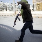 A Free Syrian Army fighter runs for cover during fighting against government troops in Idlib. (AP Photo/Rodrigo Abd)