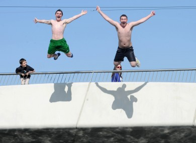 Michael Spain and Joseph McCarthy jump off Mayor Street Bridge in the IFSC into the River Liffey today