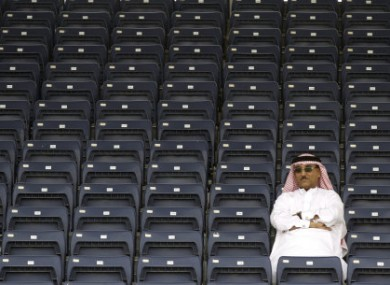 A spectator watches from an empty stand during the third free practice ahead of the Bahrain Formula One Grand Prix at the Formula One Bahrain International Circuit in Sakhir