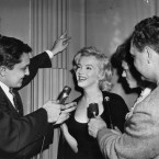 Actress Marilyn Monroe flashes radiant smile behind microphones of newsmen (AP Photo)