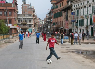 Nepalese boys play football on a traffic free street in Katmandu, Nepal