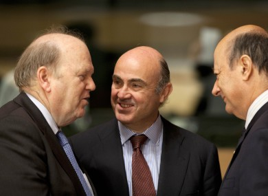 Finance Minister Michael Noonan, Spain's Economy Minister Luis de Guindos and Poland's Finance Minister Jacek Rostowski share a word during a meeting of EU finance ministers at the European Council building in Luxembourg