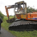 A garda walks past a fire damaged tracked machine at Clonmoylan Bog near Woodford during a standoff between National Parks and Wildlife Service over illegal turfcutting on the bog land resulted in the removal of turfcutting equipment in the presence of gardai.
