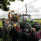 Protestors cheers as a seized hopper is driven away