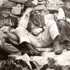 Men relax at a wall on the island - they are wearing pampooties, woollen socks and patched trousers.