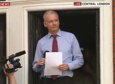 Julian Assange acknowledges supporters before speaking from a balcony at the Ecuadorian embassy in London.