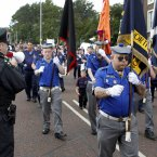 A police officer attempts to stop a loyalist band from playing music outside St Patrick's. (AP Photo/Peter Morrison/PA)