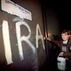 An IRA supporter paints on the wall of the Springfield Road Police Station just as the ceasefire came into being. Image: McCullou/PA Archive