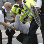 British police officers arrest a man as rioters gather in Croydon, south London. 