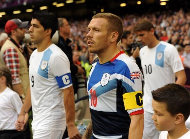 Great Britain captain Craig Bellamy (right) and Uruguay's Luis Suarez walk out prior to the group A match against Uruguay at the Millennium Stadium last night.