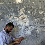 A Syrian man holds bullets he picked from a wall in a damaged house in town of Atareb outskirts of Aleppo, Syria. (AP Photo/Khalil Hamra)