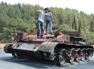 A Syrian man flashes the victory sign as he stands with his friend atop of a burned Syrian military tank which was destroyed during a clashes between Syrian forces and rebels in Saraqeb.