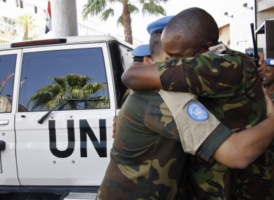 United Nations observers embrace upon arrival in Damascus, Syria from Homs, as they prepare to depart the country today