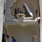 Syrians salvage what they can of their belongings from a building that was hit during a Syrian government airstrike in Aleppo, Syria. (AP Photo/ Khalil Hamra)