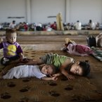 Syrian children, who fled their home with their family due to fighting between the Syrian army and the rebels, lie on the ground, while they and others take refuge at the Bab Al-Salameh border crossing, in hopes of entering one of the refugee camps in Turkey, near the Syrian town of Azaz. (AP Photo/Muhammed Muheisen)