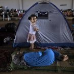 A three-year-old Syrian girl, Raghad Hussein, stands by her family's makeshift tent at the Bab Al-Salameh border crossing. (AP Photo/Muhammed Muheisen)