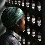 A Nepalese boy looks out from one of the windows of a Mosque as others offer Eid al-Ftr prayer, in Katmandu, Monday. Muslims around the world are celebrating Eid al-Fitr, marking the end of Ramadan, the Muslim calendar's ninth and holiest month during which followers are required to abstain from food and drink from dawn to dusk. (AP Photo/Niranjan Shrestha)