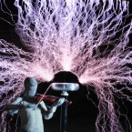 A man plays violin as up to 1 million volts, generated by a Tesla coil transformer, runs through his body during a stunt. Wang Zengxiang has dedicated himself to a dare-devil career for a decade. (Photo by Liu Tao/ChinaFotoPress)