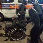 A man in a wheelchair is helped by riot police in Tottenham, north London as trouble flared after members of the community took to the streets last night to demand justice, after Mark Duggan, 29, was shot dead by police.