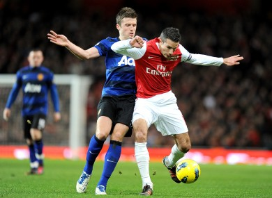 Arsenal's Robin van Persie (right) and Manchester United's Michael Carrick (left) battle for the ball.