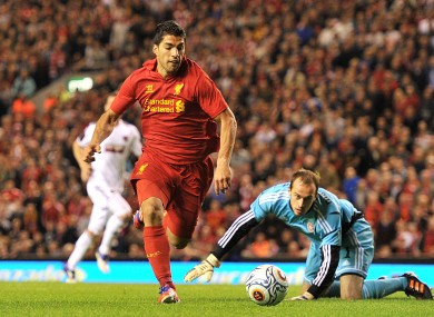Liverpool's Luis Suarez goes around Heart Of Midlothian goalkeeper Jamie MacDonald (floor) but fails to score.