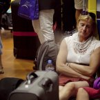 A woman sleeps by a suitcase as displaced people from Valle Gran Rey Village, wait to be evacuated at San Sebastian harbor in La Gomera, Spain, Monday, Aug. 13, 2012.  (AP Photo/Andres Gutierrez)
