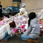 Two mourners comfort each other at the makeshift shrine for Tia Sharp near her grandmother's home in New Addington, Croydon. Max Nash/PA Wire