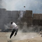 An Egyptian protester throws back a tear gas canister toward riot police, unseen, behind cement blocks that are used to close the street leading to the US embassy during clashes in Cairo, Egypt, today.  