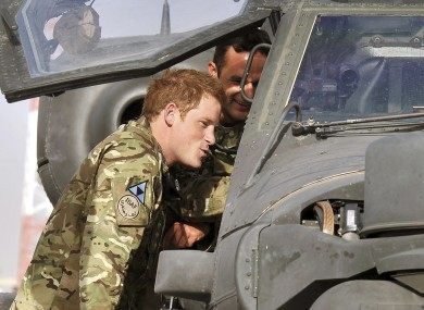 File photo of Prince Harry examining an Apache helicopter with a member of his squadron at Camp Bastion